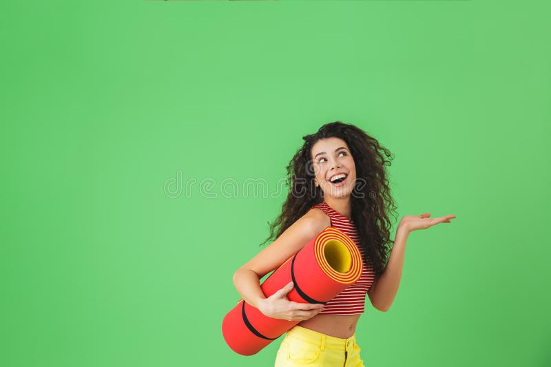 Photo of athletic woman 20s smiling and carrying yoga mat during workout stock photo