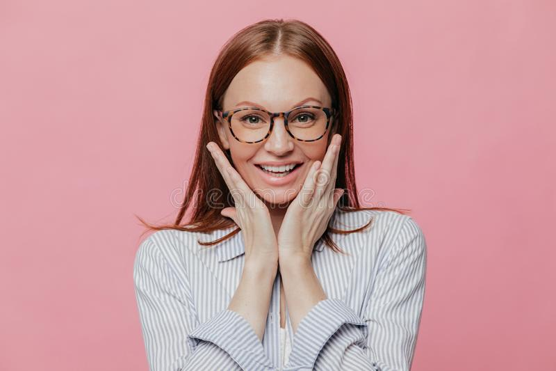 Photo of atractive young woman teacher with toothy smile, touches cheeks, happy to recieve praise, wears formal shirt, likes her royalty free stock images