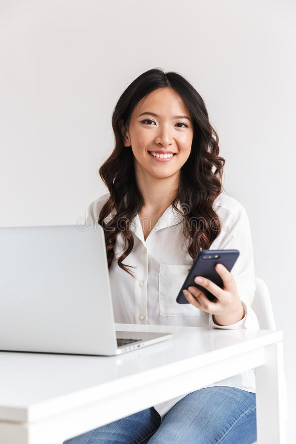 Photo of attractive asian office woman with long dark hair sitting at table and holding smartphone while working with laptop, iso royalty free stock photography