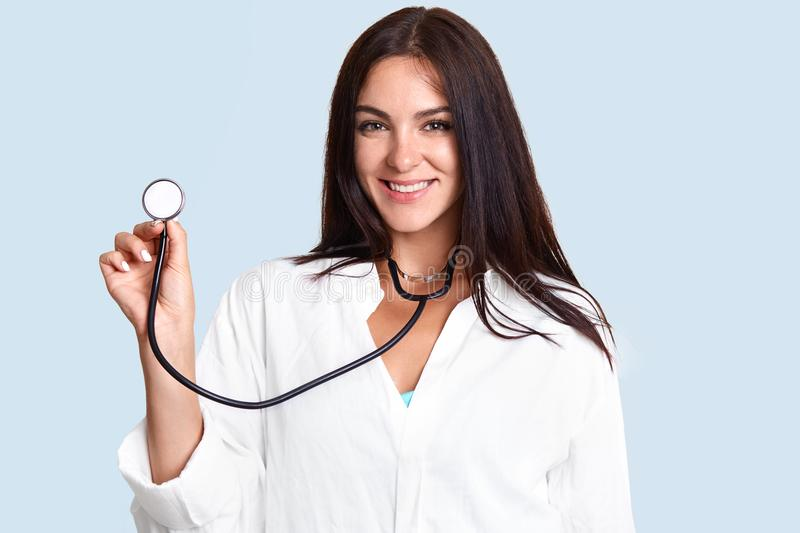 Photo of attractive brunette young female pulomonologist listens patient`s lungs, diagnoses acute bronchitis, wears lab coat, stan stock photos