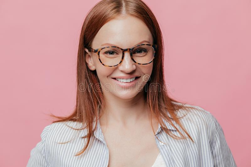 Photo of attractive cheerful young woman with glad satisfied expression, brown hair, smiles broadly, wears spectacles, delighted stock photography