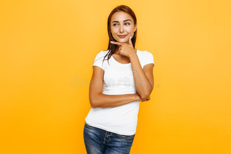 Photo of an attractive cute sly girl pointing her finger at the void  on a yellow background stock image