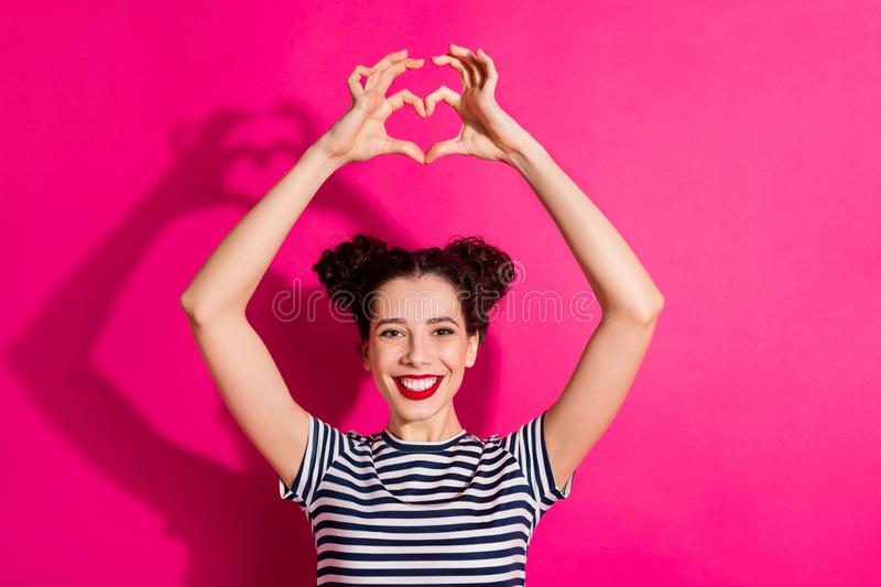 Photo of attractive cute nice charming girlfriend casting shadow showing you heart shape sign smiling toothily isolated royalty free stock image