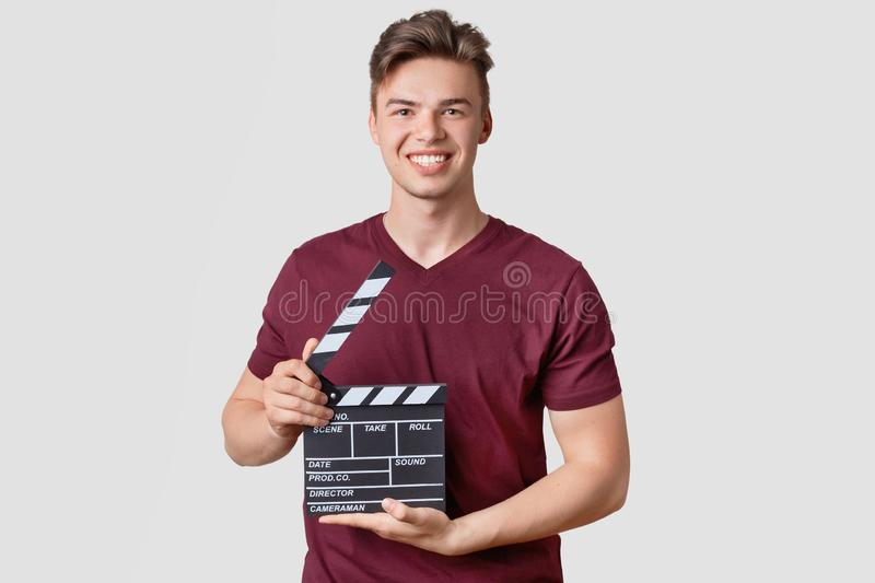 Photo of attractive guy with stylish hairdo, holds clapperboard, being producer of new film, smiles broadly, wears casual t shirt. stock photo