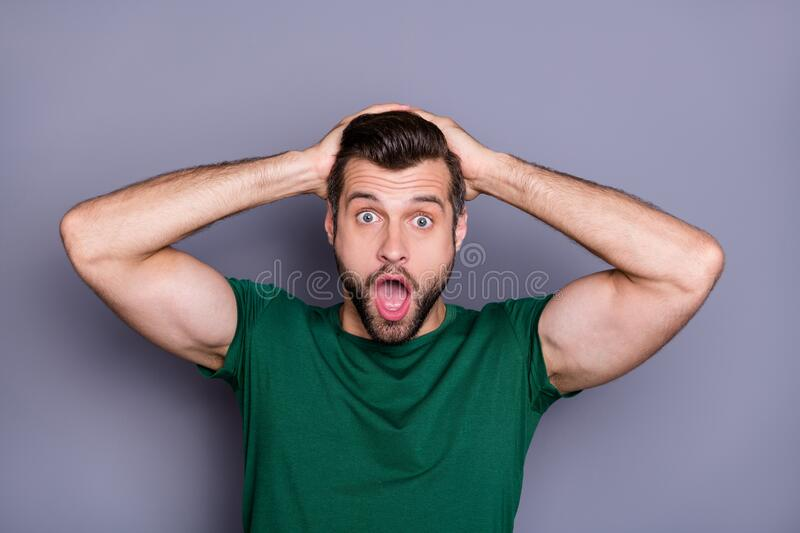 Photo of attractive handsome bearded guy open mouth arms on head watch tv news listen horrible coronavirus disease. Photo of attractive handsome bearded guy open royalty free stock images