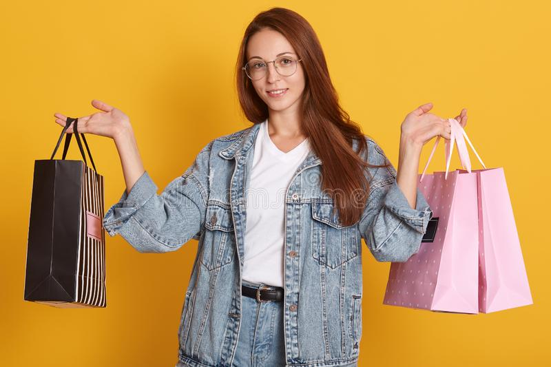 Photo of attractive happy stylish woman shopaholic holding shopping bags over yellow studio background, wearing denim jacket, royalty free stock images