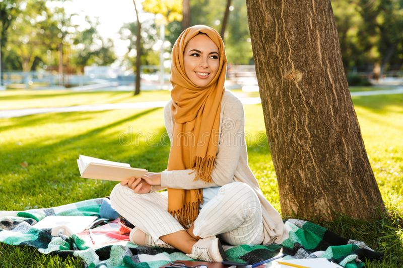 Photo of attractive islamic female student wearing headscarf sitting on blanket in green park royalty free stock photos