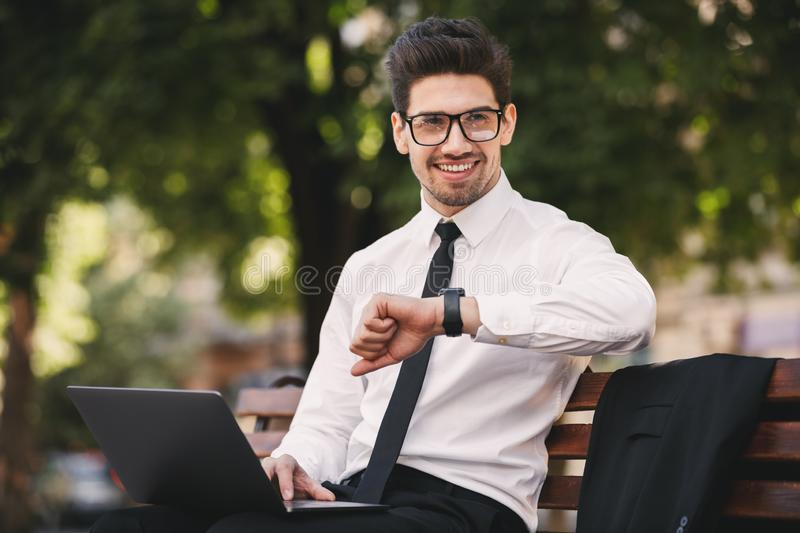 Photo of attractive man in businesslike suit working on laptop i. N green park and looking at wristwatch royalty free stock photo