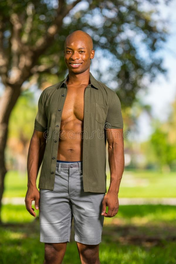 Photo attractive young bald black man smiling at camera. African American male model enjoying holiday in the park royalty free stock photography