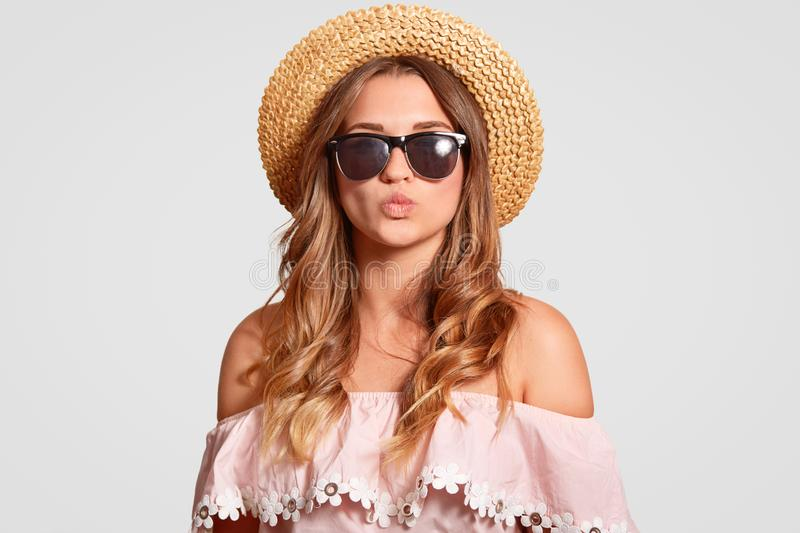 Photo of attractive young European female has summer vacation, going on beach, dressed in fashionable blouse, shows bare shoulders stock image