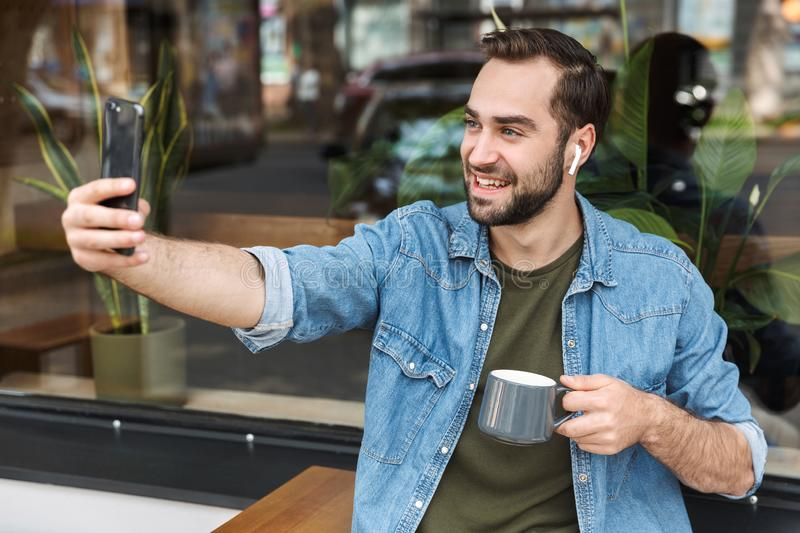 Photo of attractive young man drinking cup of coffee while taking selfie on smartphone in city cafe outdoors stock images