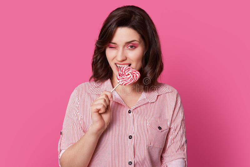 Photo of attractive young woman with dark haired woman with bright makeup, bites candy, blinks eye, poses over pink background, stock photography