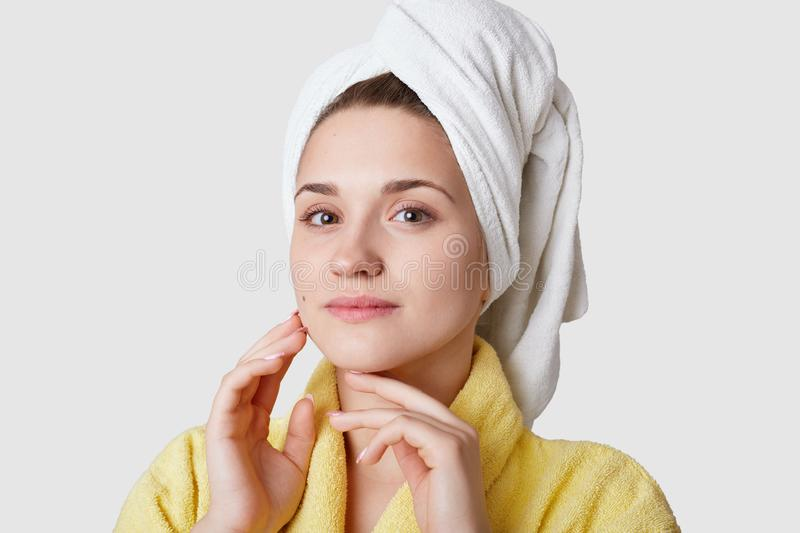 Photo of attractive young woman with tender soft skin, looks directly at camera, has white towel on face, models over white. Background, prepares for spa royalty free stock photo