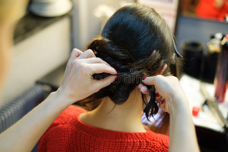 Photo from back of brunette and stylist doing hairstyle royalty free stock photography