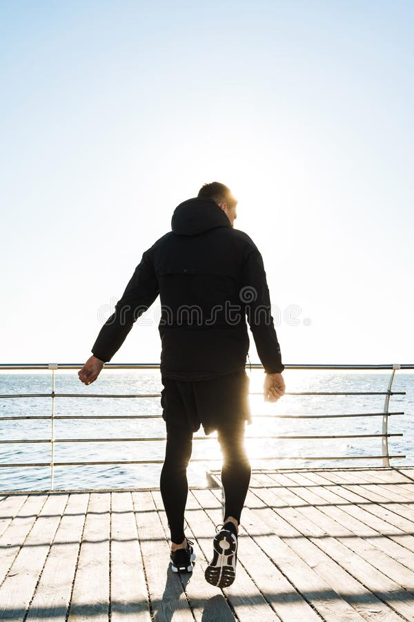 Photo from back of caucasian guy walking along wooden boardwalk by seaside after morning workout royalty free stock photography
