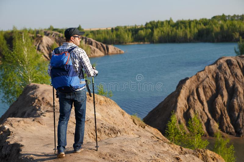 Photo from back of tourist man in cap with walking sticks on mountain hill near lake. During day royalty free stock photo