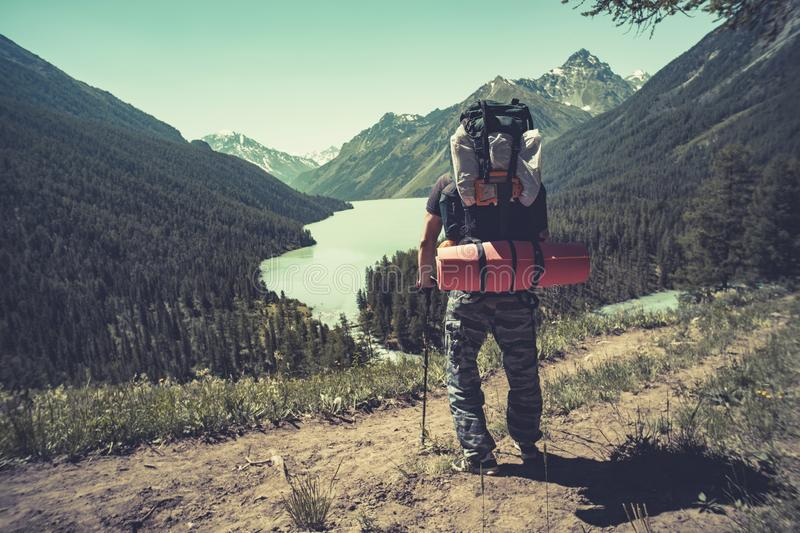 Photo from back of tourist man in cap with walking sticks on mountain hill near lake. tourist holding sticks. For Nordic walking stock photos