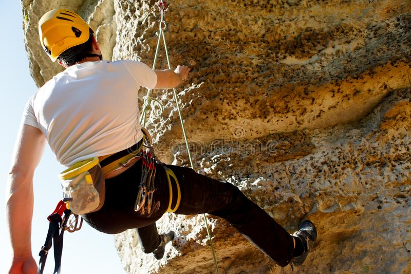 Photo from back of tourist`s man in helmet and white T-shirt climbing up mountain to top royalty free stock photo