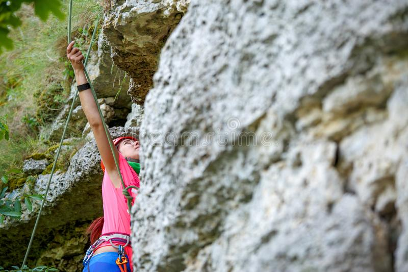 Photo from back of young sports woman in red helmet climbing up mountain to top stock photos
