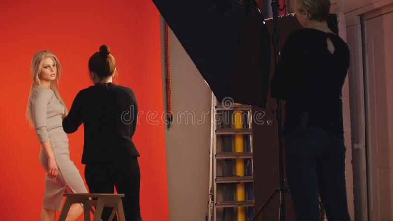 Photo backstage: blonde girl model plays long hair - photographer take a picture in studio. Red background royalty free stock photo