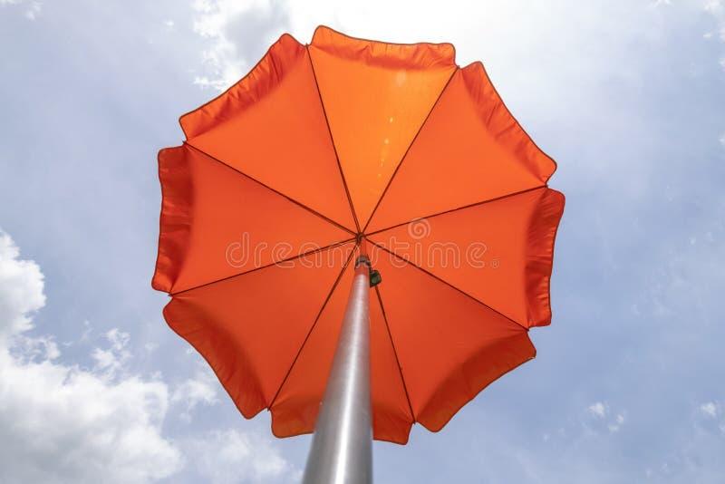 Photo of a beach umbrella on the blue sky,Beach umbrella.One vibrant orange colored sunshade against vivid blue sky and white. Cloud, parasol, summer, travel stock photos