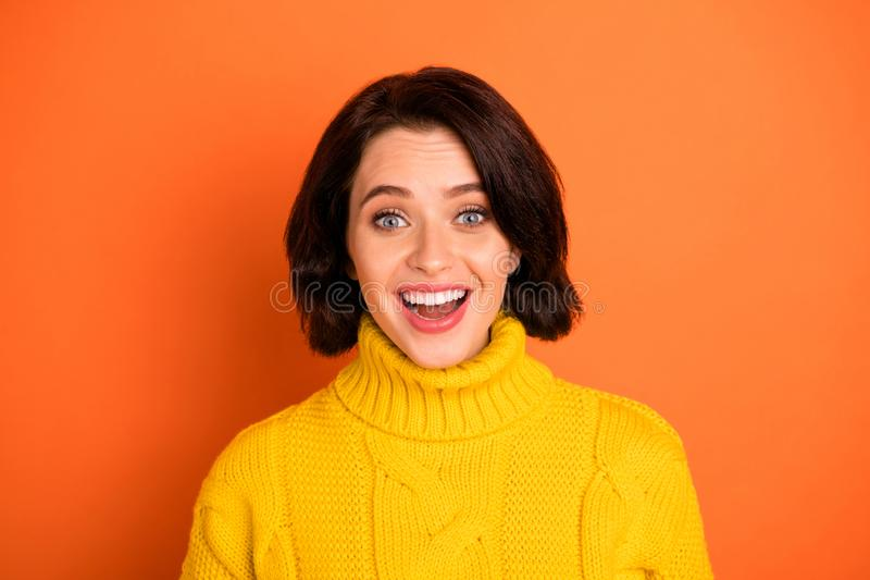 Photo of beaming cheerful carefree interested woman seeing prices decreased while isolated with orange background. Photo of beaming cheerful carefree, interested royalty free stock photo