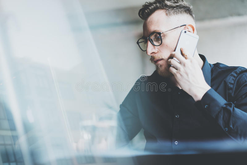 Photo bearded adult manager working on modern urban cafe. Man wearing black shirt and talking contemporary smartphone stock photo