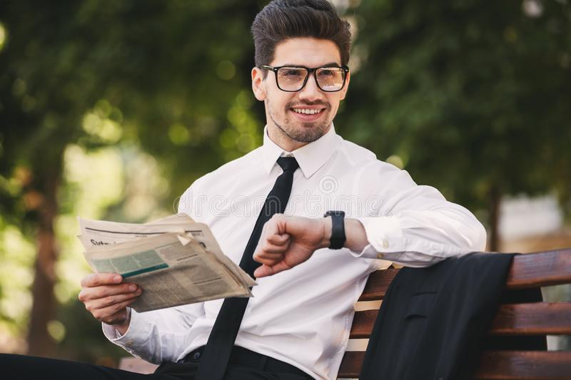 Photo of bearded man in businesslike suit reading newspaper on b. Ench in green park and looking at wristwatch stock photos