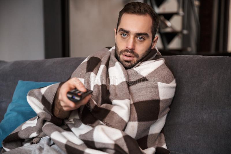 Photo of bearded man 30s being ill while sitting wrapped in blanket on sofa at home stock photo