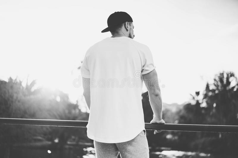 Photo Bearded Muscular Man Wearing Blank t-shirt, snapback cap and shorts in summer time. Green City Garden Park Sunset. Background. Back view. Horizontal royalty free stock images