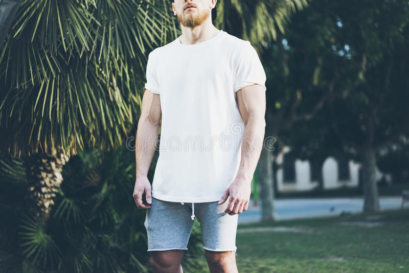 Photo Bearded Muscular Man Wearing White Blank t-shirt and shorts in summer time. Green City Garden Background,blurred royalty free stock images
