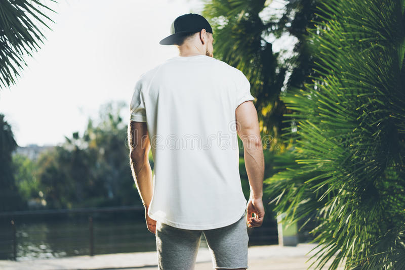 Photo Bearded Muscular Man Wearing White Blank t-shirt, snapback cap and shorts in summer time. Green City Garden Park. Background. Back view. Horizontal Mockup stock photos