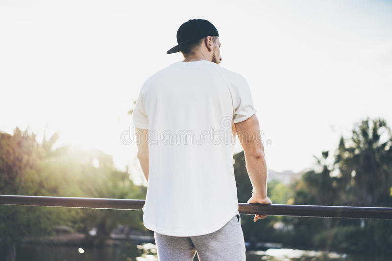 Photo Bearded Muscular Man Wearing White Blank t-shirt, snapback cap and shorts in summer time. Green City Garden Park. Sunset Background. Back view. Horizontal royalty free stock photography