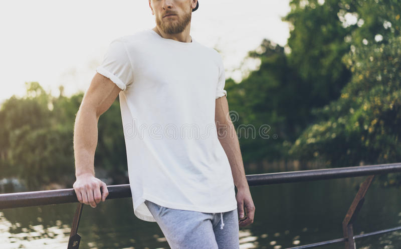 Photo Bearded Muscular Man Wearing White Empty t-shirt, snapback cap and shorts in summer holiday. Relaxing time near. The lake. Green City Garden Park Sunset stock images