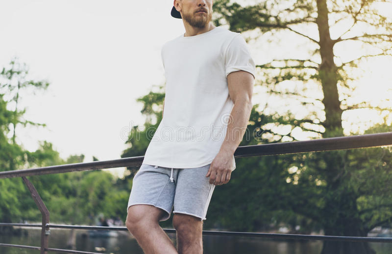 Photo Bearded Muscular Man Wearing White Empty t-shirt, snapback cap and shorts in summer vacation. Relaxing time near. The lake. Green City Garden Park Sunset stock photography