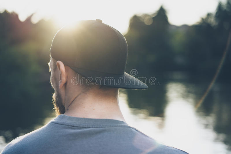 Photo Bearded Young Man Wearing Black Blank Cap. Green City Park Lake Background and Sunset effect. Back view royalty free stock images