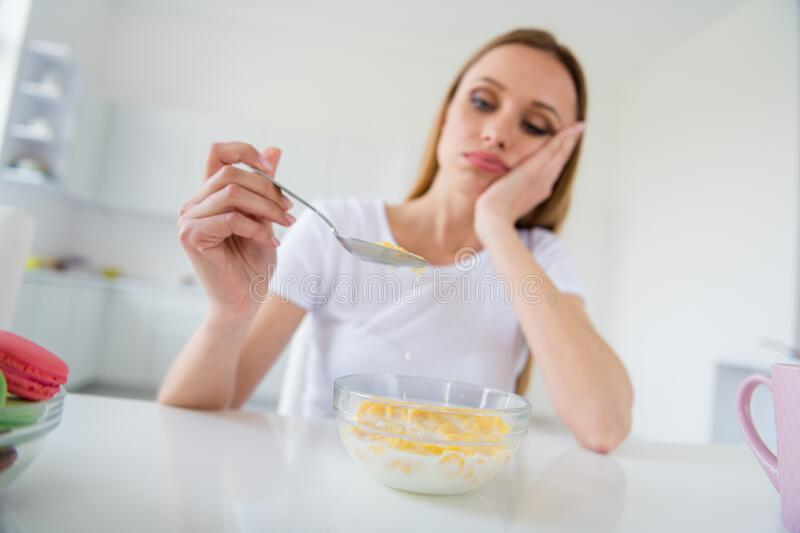 Photo of beautiful blond upset housewife holding spoon don`t want eat milk breakfast cornflakes tired of dieting bored royalty free stock photo