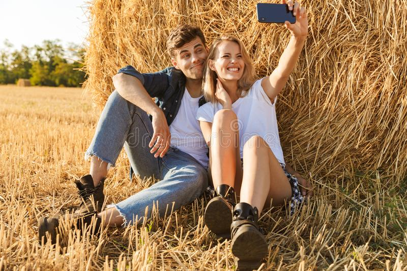 Photo of beautiful couple man and woman taking selfie while sitting under big haystack in golden field, during sunny day. Photo of beautiful couple men and women royalty free stock photography