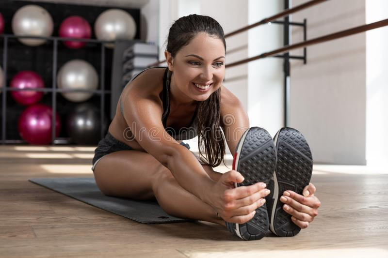 Photo of a beautiful female stretching on the floor sitting on a mat. royalty free stock image