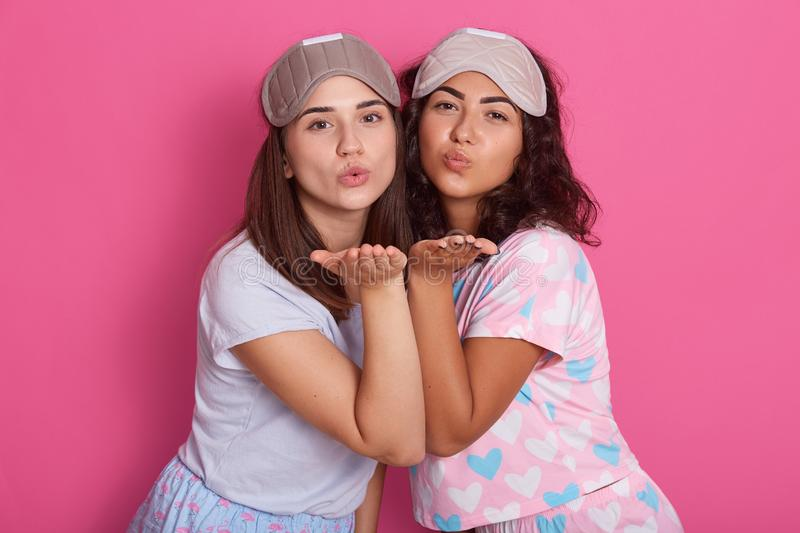 Photo of beautiful girls posing in pajamas. Studio shot of two friends standing on pink background and shows air kisses, having stock photo