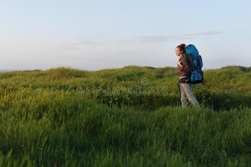 Beautiful hiker woman walking in the meadow with trekking backpack royalty free stock photography