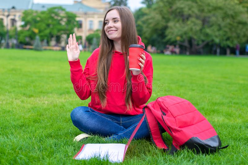 Photo of beautiful king cheerful excited funky person sitting on green grass waving palm enjoying summer drinking takeaway takeout. Beverage stock image