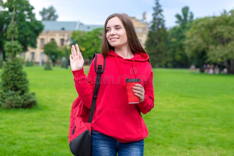 Photo of beautiful lady enjoying nice takeaway takeout beverage latte tea going to lessons waving palm to somebody.  royalty free stock photo