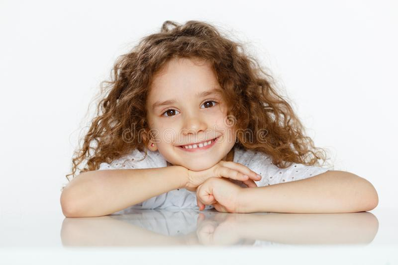 Adorable little cute girl with curly hair in white blouse, seated at a table, looking at camera, over white background. stock photo