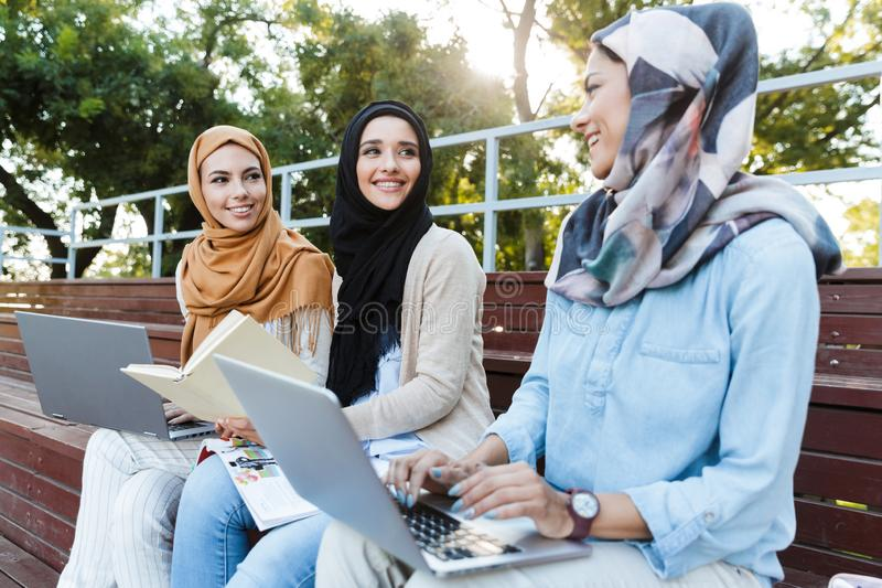 Photo of beautiful muslim girls wearing headscarfs resting in green park royalty free stock photography