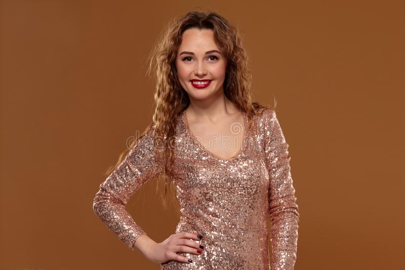 Portrait of young caucasian female in golden cocktail dress looking into the camera on brown background stock photography