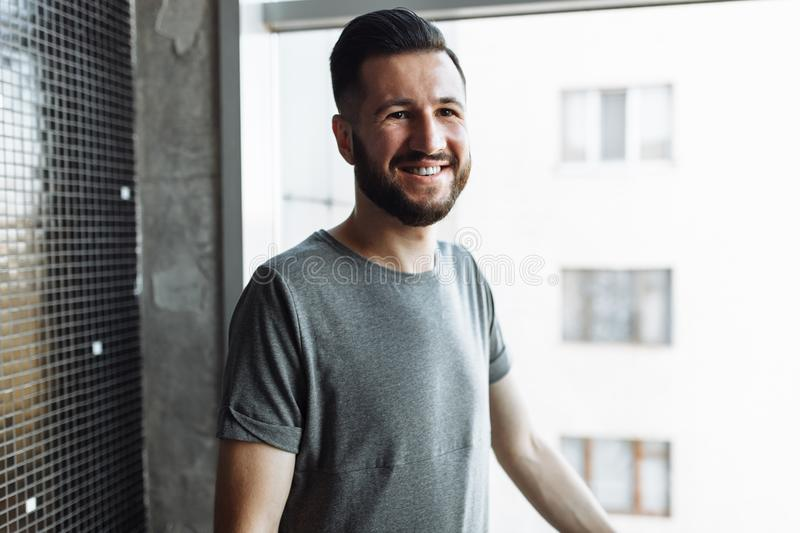 Photo of a beautiful stylish guy, hipster, dressed in a gray empty t-shirt, standing near the window, on a black wall background. stock photography