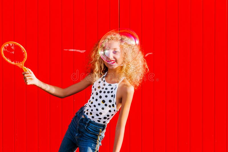 Beautiful teenage girl inflates soap bubbles against the red wall royalty free stock photography