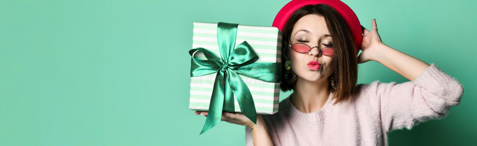 Photo of beautiful woman in felt hat holding present gift box royalty free stock images