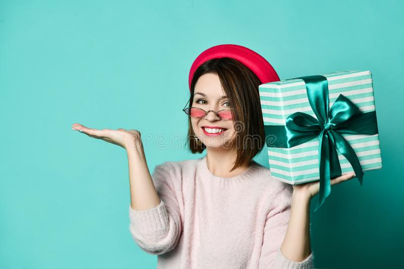 Photo of beautiful woman in felt hat holding present gift box royalty free stock photography